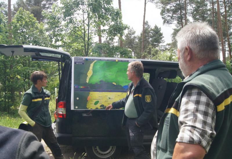 Forstmitarbeiter betrachten eine Karte im Freien.