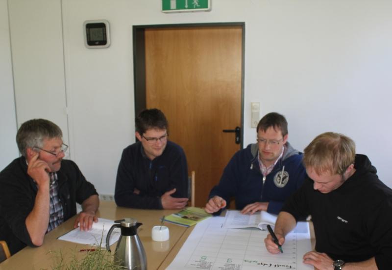 Vier Personen sitzen an einem Tisch und arbeiten an einer Flichart