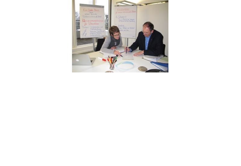 Zwei Personen sitzen am Tisch und arbeiten am Thema Klimaschutz und Anpassung an den Klimawandel