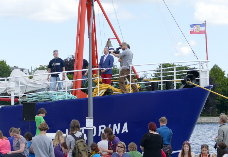 Menschenmenge vor einem Schiff, auf dem Redner und Kameramann stehen.