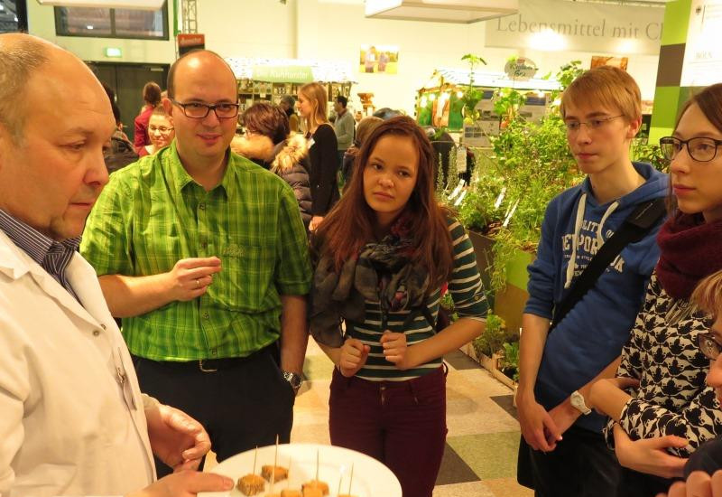 Mehrere Veranstaltungsbesucher stehen um den Anbieter von veganen Lebensmitteln.