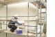 Das Bild zeigt einen Mann mit Bauhelm, der auf einem Baugerüst hockt und eine Dämmplatte an der Hauswand anbringt.