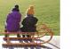 Das Bild zeigt zwei Kinder von hinten, die mit Pudelmützen und Winterjacken nebeneinander auf einem Schlitten sitzen, der auf einer Holzterrasse vor einer grünen Wiese steht.