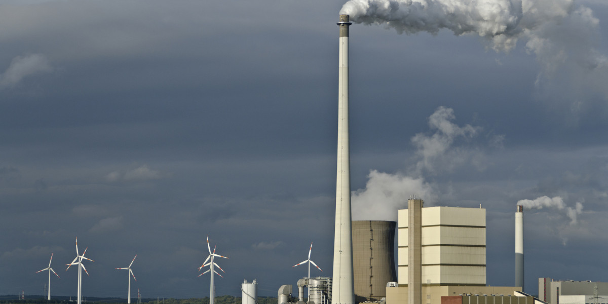 power plant with smoking chimney and wind power plants