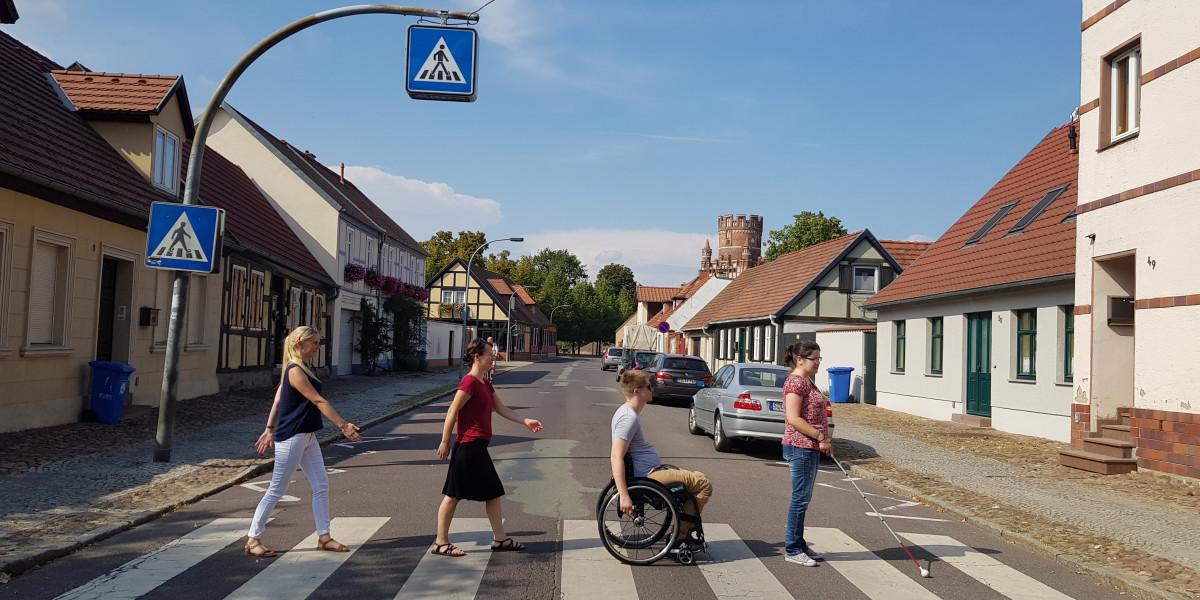 Straße mit niedrigen Fachwerkhäusern und einem Zebrastreifen, der von einer Frau mit Blindenstock, einem Rollstuhlfahrer und zwei weiteren Fußgängerinnen überquert wird.