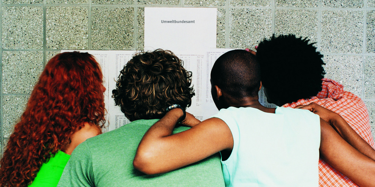 Vier junge Menschen beugen sich über eine Pinnwand mit Aushängen