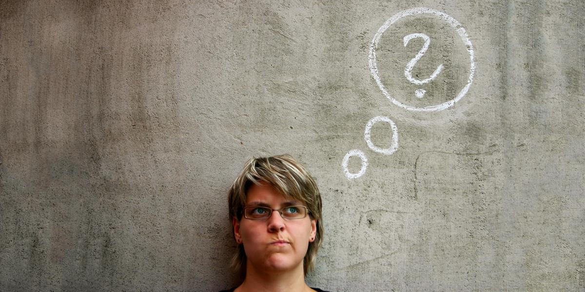 Eine Frau mir fragendem Blick steht vor einer Wand, auf die mit Kreide ein Fragezeichen gemalt ist.