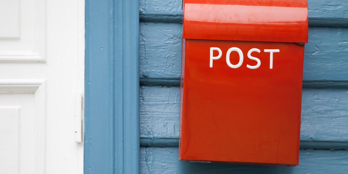 Ein roter Briefkasten hängt an einer Hauswand