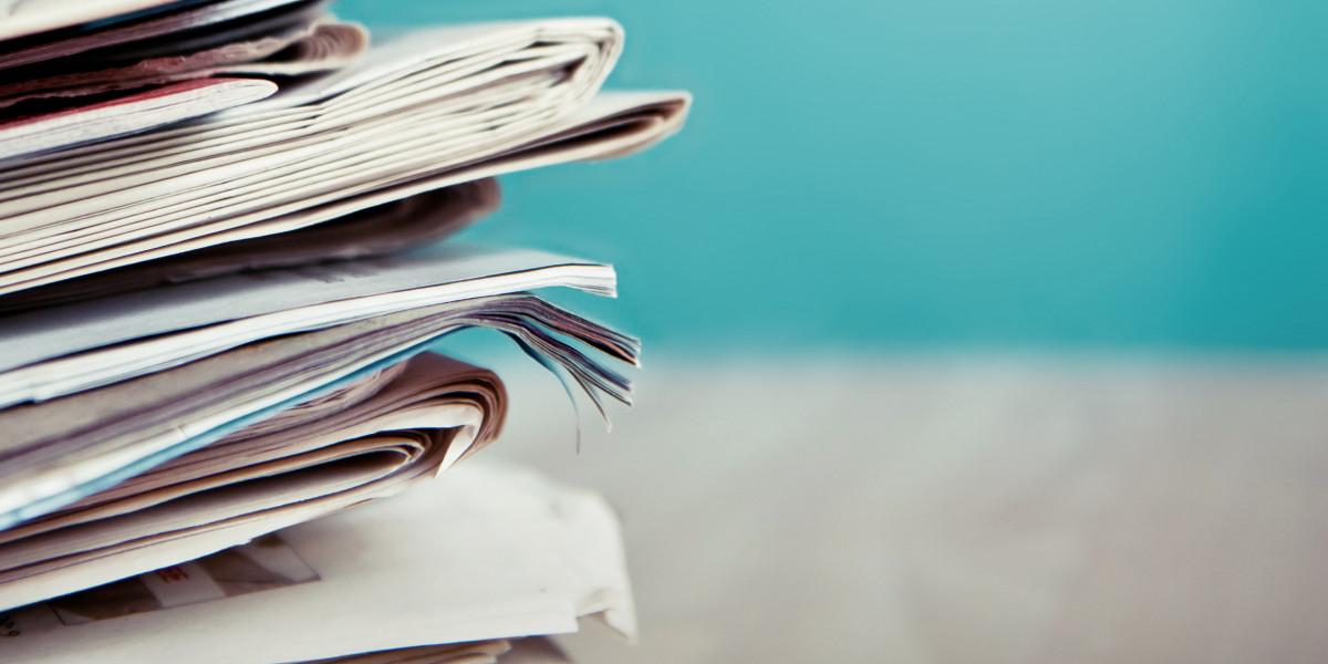 Ein Stapel von Zeitungen liegt auf einem Tisch.