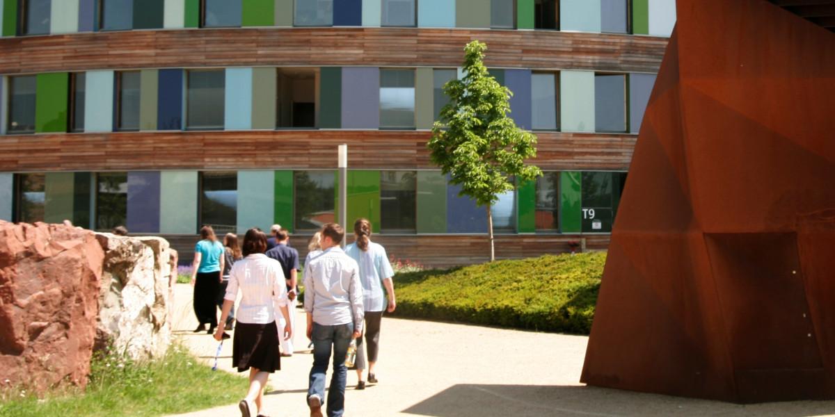Beschäftigte des UBA gehen zum Haupteingang des UBA-Dienstsitzes in Dessau-Roßlau