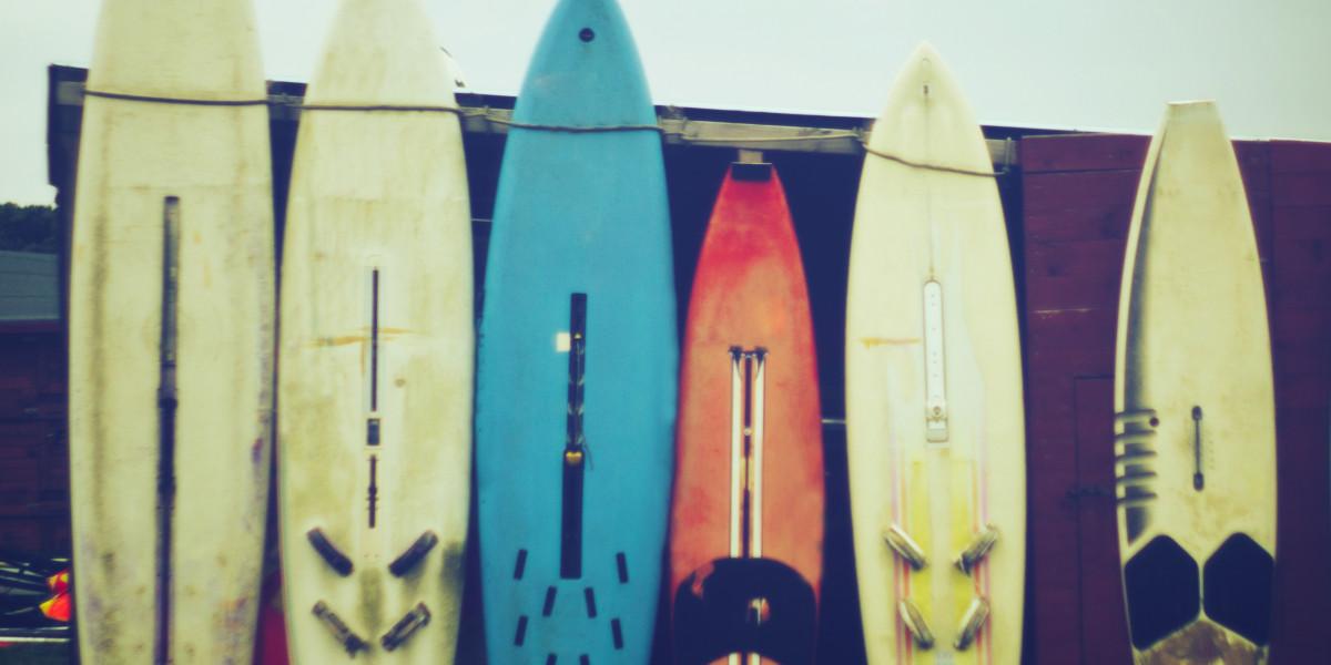 Sechs Surfbretter lehnen an einer Garage