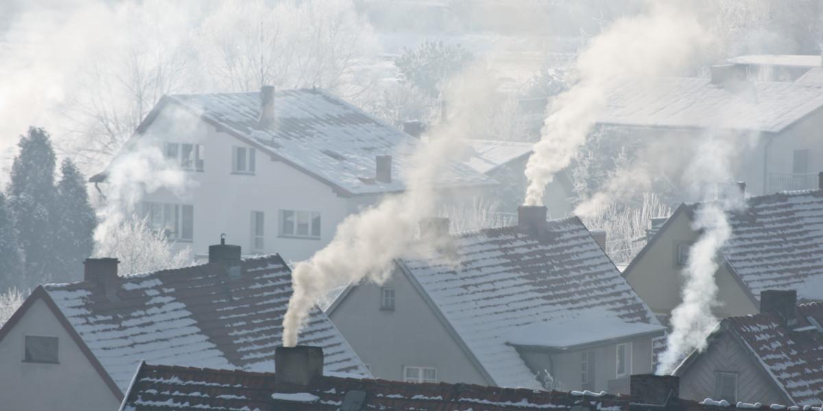 Über verschneiten Dächern qualmen etliche Schornsteine